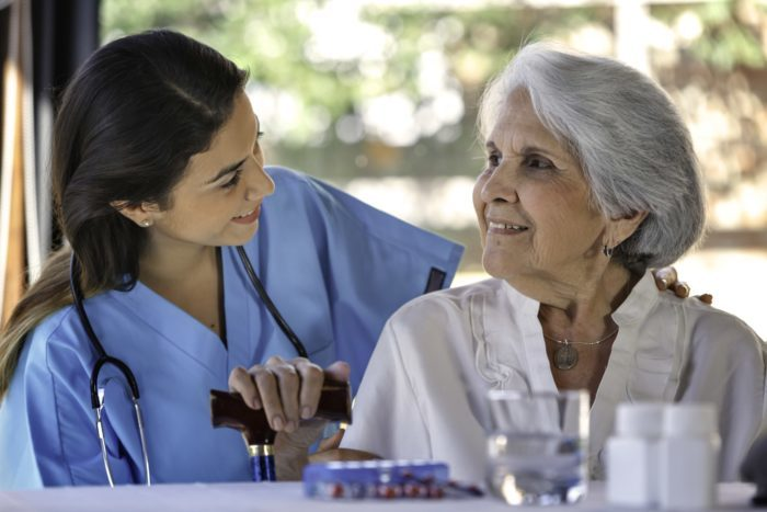 Nurse speaking with a seated woman holding a walking stick