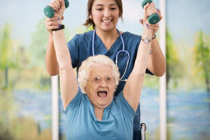 Nurse helping a seated woman raise dumbbells above her head