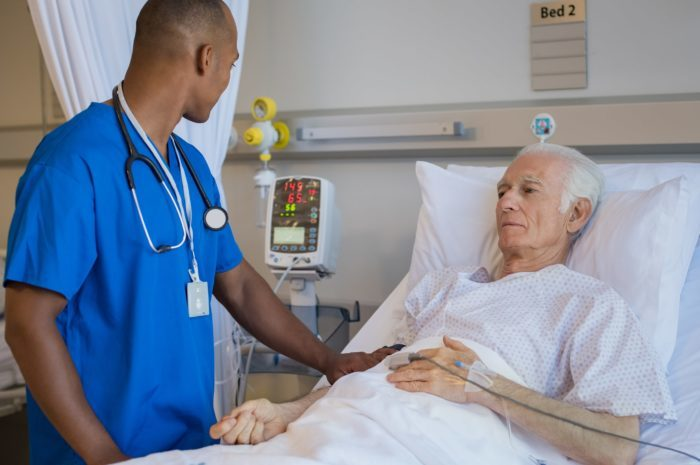 Nurse speaking to a man in bed
