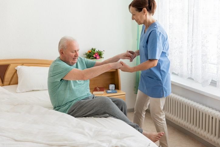 Nurse grabing both hands of a man to help him get up from bed
